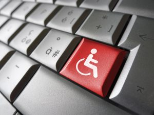 Web content accessibility concept with wheelchair icon and symbol on a red computer key for blog and online business.